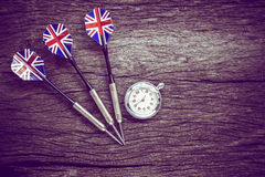 Darts and watch on old wooden background. Royalty Free Stock Photo