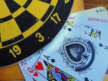 Dartscheibe mit Karten und Würfel auf Schachbrett Lizenzfreie Stockbilder