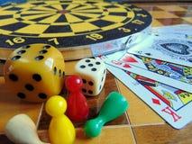 Dartscheibe mit Karten und Würfel auf Schachbrett Stockfotografie