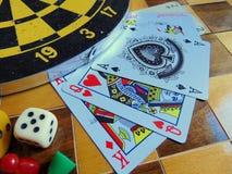 Dartscheibe mit Karten und Würfel auf Schachbrett Stockbilder