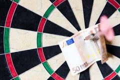 Dartscheibe mit Stahlpfeilen und Euro in ihm Lizenzfreies Stockfoto