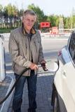 Das ältere europäische Mannfüllen besitzen Auto mit Benzin in den Tankstellen lizenzfreie stockfotografie