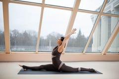 Das übende Yoga der jungen attraktiven Frau, sitzend im Affe-Gott, spaltet Übung, Hanumanasana-Haltung, das Ausarbeiten auf und t Stockbilder