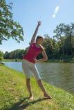 Das übende Yoga der jungen Frau durch den See Lizenzfreie Stockbilder