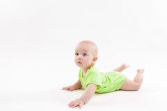 Das überraschte nette Baby, das auf seinem Magen liegt und betrachtet, kam Stockfoto