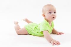 Das überraschte nette Baby, das auf seinem Magen liegt und betrachtet, kam Stockfotos