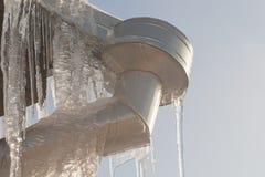 Das Abflussrohr und die Fassade des Gebäudes werden mit Eiszapfen bedeckt gefrorener Abwasserkanal lizenzfreie stockfotografie