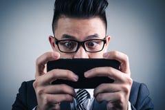 Das abstrakte Bild des Gamer, der Videospiel durch den Smartphone spielt lizenzfreie stockfotografie