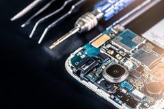 Das abstrakte Bild des Smartphone ` s Motherboards und der Werkzeuge, die auf Tabelle legen und der schwarze Kopienraum ist Hinte stockfoto