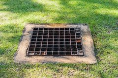 Das Abwasserkanalgitter auf dem Rasen Stockfotografie