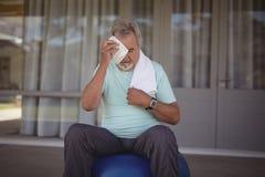 Das Abwischen des älteren Mannes schwitzte weg von seinem Gesicht mit Tuch Stockfoto