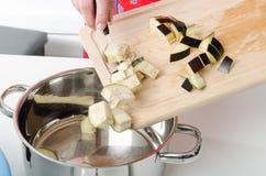 Das Addieren der Aubergine bessert in Kasserolle aus Lizenzfreie Stockfotografie