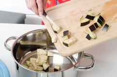 Das Addieren der Aubergine bessert in Kasserolle aus Stockbilder