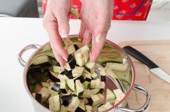 Das Addieren der Aubergine bessert in Kasserolle aus Lizenzfreie Stockfotos