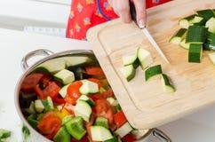 Das Addieren der Zucchini bessert in Kasserolle aus Lizenzfreie Stockbilder