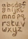 Das Alphabet geschrieben in Sand. Stockfotografie