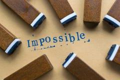 das Alphabetbuchstabewort, das vom Stempel unmöglich ist, beschriftet Guss auf Papier Stockfotografie
