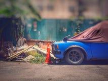 Das alte blaue Auto wird mit braunem Stoff in der Tageszeit geparkt, stockbilder