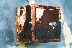 Das alte elektrische Schild hängt an der exfoliating Wand des Hauses, ein rostiger Metallkasten, der an der Wand hängt Stockbild
