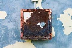 Das alte elektrische Schild hängt an der exfoliating Wand des Hauses, ein rostiger Metallkasten, der an der Wand hängt Lizenzfreie Stockfotos
