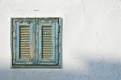 Das alte Fenster mit blauen Blendenverschlüssen auf einer weißen Wand Stockfotografie
