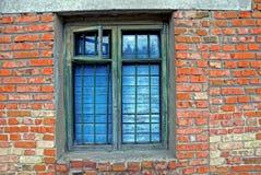 Das alte Fenster mit einem Fensterblatt oben verschalt und ein Gitter auf einer Backsteinmauer Lizenzfreie Stockbilder