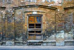 Das alte gebrochene genagelte-oben Fenster auf der Backsteinmauer Stockfoto