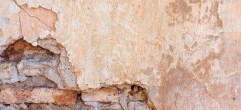 Das alte gebrochene verwitterte schäbige gemalte Gelb vergipste abgezogenen Backsteinmauer-Fahnen-Hintergrund Stockfotos