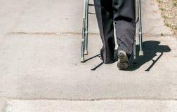 Das alte Gehen der behinderten Frau allein und deprimiert auf der Straße in der Stadt half durch justierbaren Wandererstock oder  Lizenzfreie Stockfotos