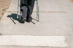 Das alte Gehen der behinderten Frau allein und deprimiert auf der Straße in der Stadt half durch justierbaren Wandererstock oder  Stockbild
