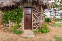 Das alte Häuschen, das von den Baumstämmen mit geschlossener hölzerner brauner Schmutztür gemacht wird und decken das Dach mit St Lizenzfreies Stockfoto