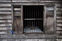 Das alte hölzerne Fenster in der hölzernen Wand Stockfoto