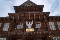 Das alte hölzerne Gebäude mit einem Engel der weißen Weihnacht Lizenzfreies Stockfoto