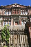 Das alte Haus des roten Backsteins mit einem hohen Zaun auf Himmelhintergrund lizenzfreie stockfotos