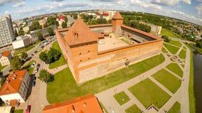 Das alte Schloss von Prinzen Gedimin in der Stadt von Lida belarus Schattenbild des kauernden Geschäftsmannes Stockfotografie