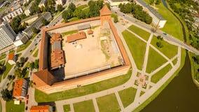 Das alte Schloss von Prinzen Gedimin in der Stadt von Lida belarus Schattenbild des kauernden Geschäftsmannes Lizenzfreie Stockbilder