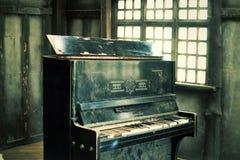 Das alte schwarze defekte Klavier stockfoto