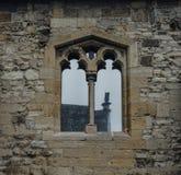 Das alte und alte Fenster mit Glasreflexion in der Steinwand Lizenzfreie Stockbilder