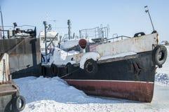 Das alte verlassene Boot wird am Pier auf dem Fluss eingefroren Lizenzfreie Stockfotografie