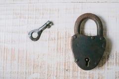 Das alte Vorhängeschloß und der Schlüssel auf einem weißen hölzernen Hintergrund Stockbild