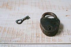 Das alte Vorhängeschloß und der Schlüssel auf einem weißen hölzernen Hintergrund Stockfotos