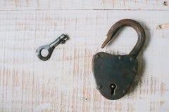 Das alte Vorhängeschloß und der Schlüssel auf einem weißen hölzernen Hintergrund Stockfotografie