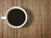 Das Anschlagbrett mit einem Tasse Kaffee auf dem Weidenhintergrund stockfoto