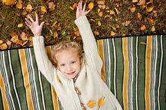 Das anziehende gelockte blonde Mädchen in der Beige strickte Strickjacke lächelnd während Stockfotografie