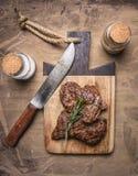 Das appetitanregende Rindfleisch, gegrillt, auf einem Schneidebrett mit Rosmarin, Gewürze und Messer für Draufsicht des hölzernen lizenzfreie stockfotografie