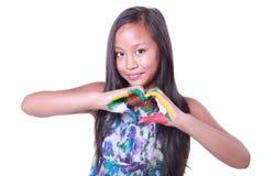 Das asiatische Mädchen, das ein Inneres mit ihr zeigt, malte Hände Stockfotografie