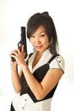 Das asiatische Mädchen mit einer Pistole Lizenzfreie Stockfotos