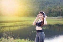 Das asiatische Mädchen trägt Kleider hörend Musik durch Kopfhörer zur Schau lizenzfreie stockfotos
