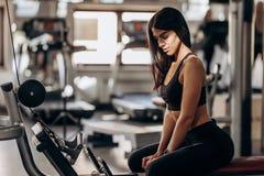 Das athletische Mädchen, das in der schwarzer Sportspitze und -strumpfhosen gekleidet wird, sitzt auf der Bank in der Turnhalle stockfoto