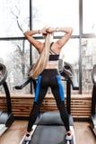 Das athletische M?dchen mit dem langen blonden Haar, das in einer Sportkleidung gekleidet wird, steht auf der Tretm?hle vor den F stockfotografie